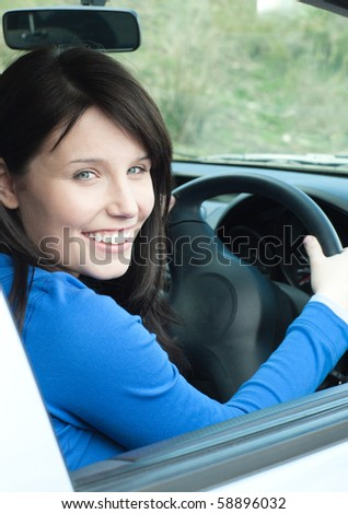 Glowing female teenager sitting in her new car smiling at the camera - stock photo