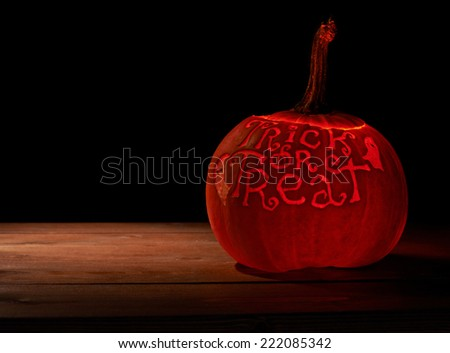 Glowing from the inside Halloween pumpkin with the words Trick or Treat carved on its surface, placed over the wooden boards in a low key dramatic lighting composition - stock photo