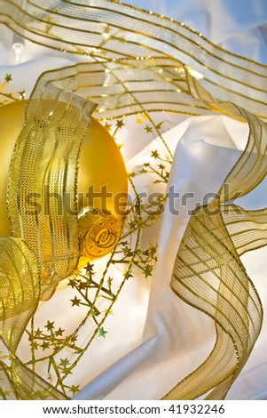 Glowing golden Christmas ornaments with transluscent ribbons, sparkling gold stars and twinkling white lights. Short depth of field with glowing effects. Good for Christmas card or background. - stock photo