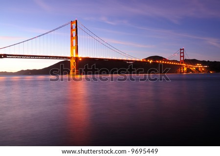 Glowing Golden Gate Bridge against a background of subtly lit clouds at sunset. Shot from Fort Point area. - stock photo