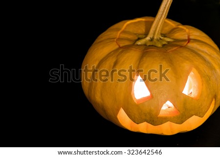 Glowing halloween pumpkin in candlelight - stock photo