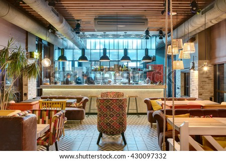 Glowing interior in a loft style in a mexican restaurant with open kitchen on the background. In front of the kitchen there are wooden tables with multi-colored chairs and sofas. On the sofas there - stock photo