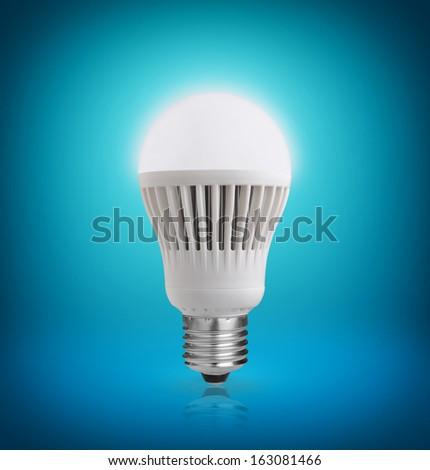 Glowing LED bulb on blue background - stock photo