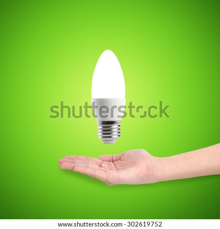 Glowing LED energy saving bulb in a hand over a green background - stock photo