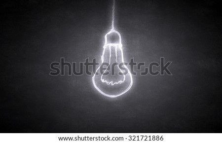 Glowing light bulb on dark background hanging from above - stock photo