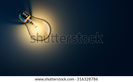 Glowing light bulb with long shadow on blue background