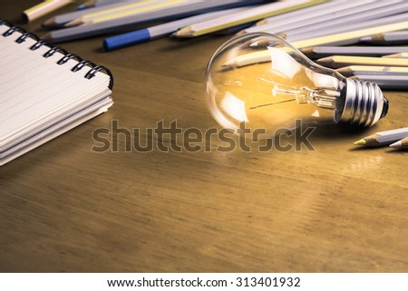 Glowing light bulb with pencils and notebook on wood table