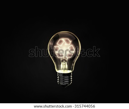 Glowing lightbulb with recycle symbol inside on dark background
