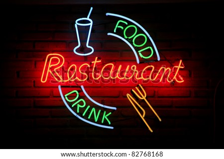 Glowing neon sign on brick wall saying restaurant food drink - stock photo