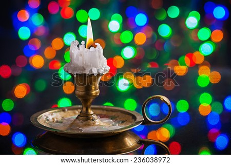 glowing old candle in wintage candlestick on surface of mirror with multycolored bokeh horizontal version - stock photo