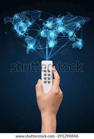 Glowing social network  world map coming out of a remote control  - stock photo