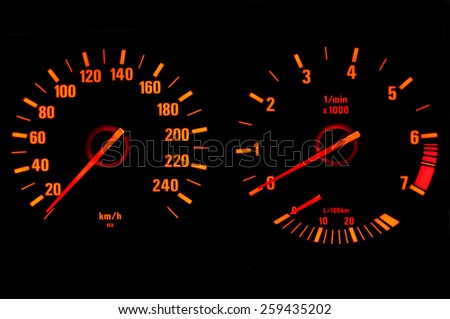 Glowing speedometer and tachometer isolated on black - stock photo