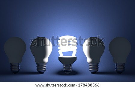 Glowing spiral light bulb in row of dead incandescent ones on dark blue textured background. Front view