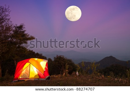 Glowing tent at night with big Moon - stock photo