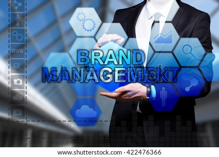 "Glowing text ""Brand Management"" in the hands of a businessman. Business concept. Internet concept."
