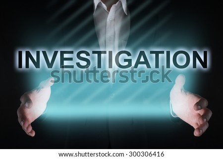 """Glowing text """"investigation"""" in the hands of a businessman. Business concept.  - stock photo"""