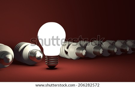 Glowing tungsten light bulb standing in row of lying switched off fluorescent ones on red textured background