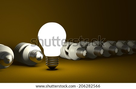 Glowing tungsten light bulb standing in row of lying switched off fluorescent ones on yellow textured background