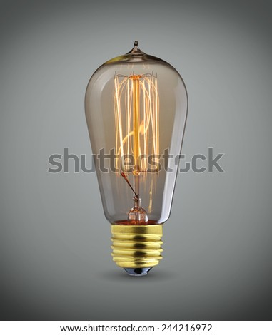 Glowing vintage  light bulb over gray background - stock photo