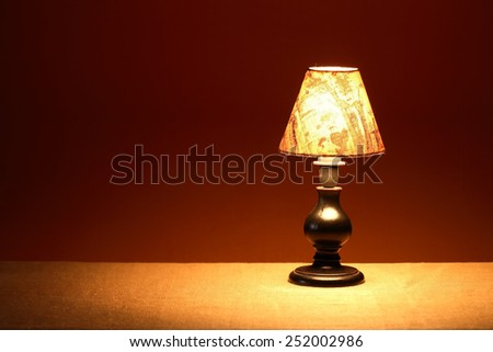 Glowing vintage table lamp with lampshade against brown wall with free space - stock photo