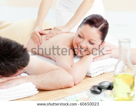 Glowing young couple receiving a back massage in a spa center