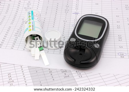 Glucometer and test strips on the background of the table glucose - stock photo