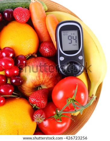 Glucometer with fresh ripe fruits and vegetables lying on wooden plate, concept of diabetes, healthy food, nutrition and strengthening immunity
