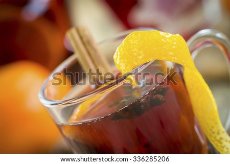Gluhwein or mulled red wine with colorful red Christmas decorations, spices and orange peel with whole fresh oranges and cinnamon for a cold winter night