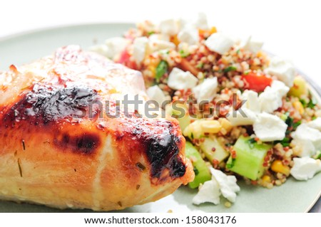gluten free chicken and salad made with quinoa, chickpeas, feta and fresh heirloom tomatoes - stock photo