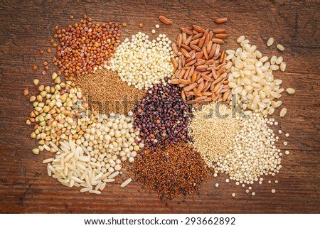 gluten free grains (buckwheat, amaranth, brown rice, millet, sorghum, teff,  red, black and white quinoa)  on rustic wood - top view - stock photo