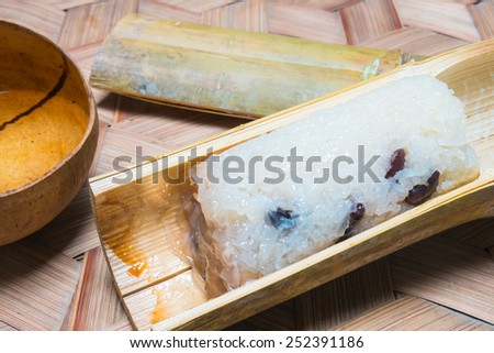 Glutinous rice roasted in bamboo joints on bamboo handcraft background