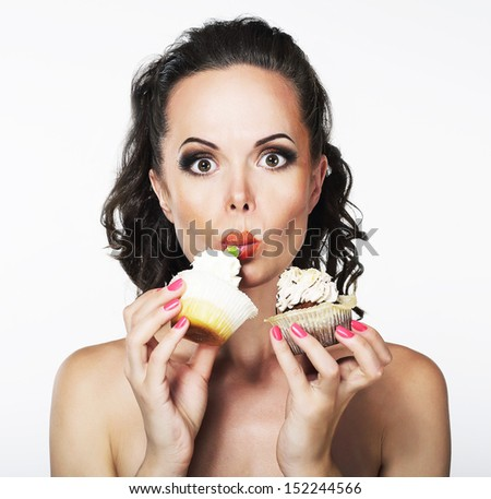 Gluttony. Hungry Funny Young Woman Greedily Eats Cakes with Cream - stock photo