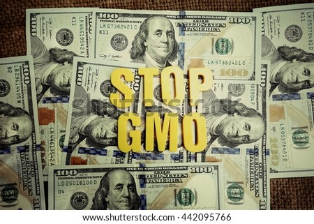 GMO concept. Yellow letters on a background of US dollars