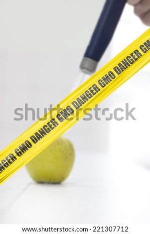 GMO Danger Cordon tape. Syringe injected in the apple. Concept of genetic modification.