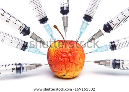 gmo / gmo food / injection of a rotten apple  - stock photo