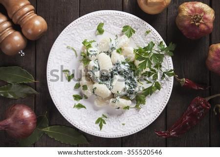 Gnocchi di patata, italian potato noodles with cheese and spinach sauce - stock photo