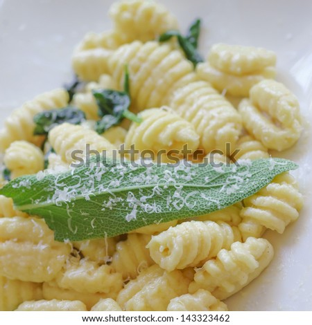 Gnocchi with butter, sage and parmesan.Italian dish. Shallow depth of field. Focus on sage. - stock photo