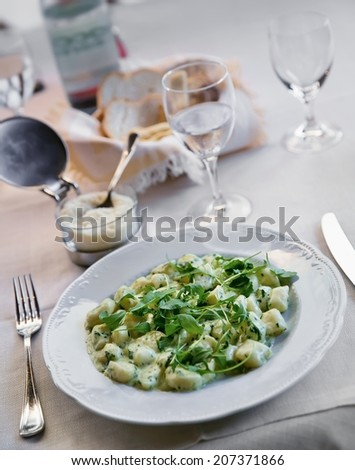 Gnocchi with cheese sauce, spring spinach and arugula - stock photo