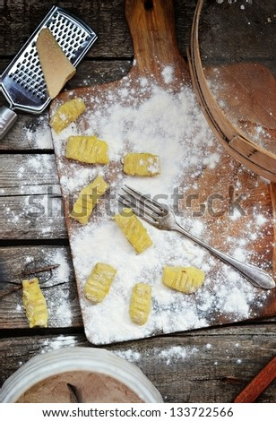 gnocci , flour and parmigano on the wooden background - stock photo