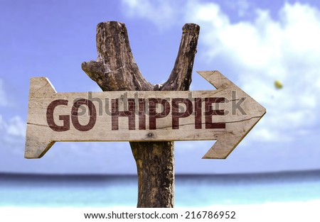 Go Hippie wooden sign with a beach on background - stock photo