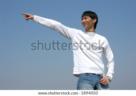 Go to the Left! Young Asian man pointing the direction - stock photo