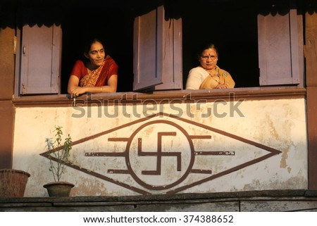 Goa, India - February 11, 2006: Woman near the window of his house with swastikas in Chaudi.