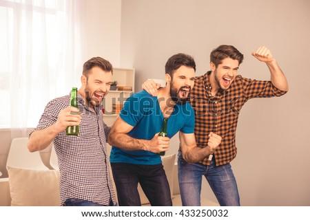 Goal!  happy joyful men at home watching sport game on tv - stock photo