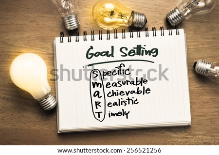 Goal setting as memo on notebook with many light bulbs - stock photo