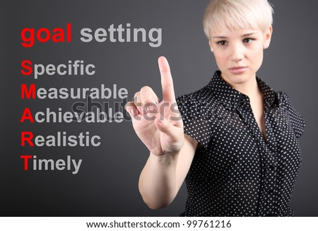 Goal setting concept - business woman touching screen - stock photo