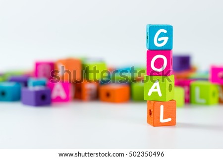 Goal word spelled with colourful wooden block over white background