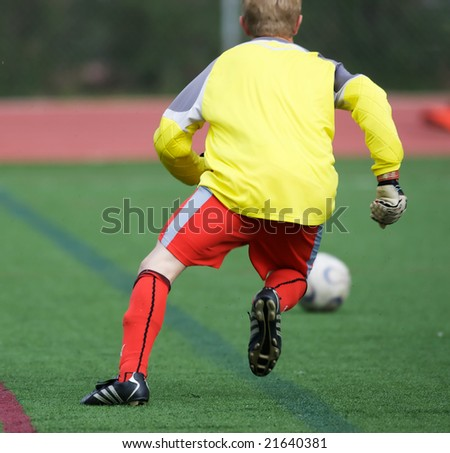 Goalie chasing after soccer ball - stock photo