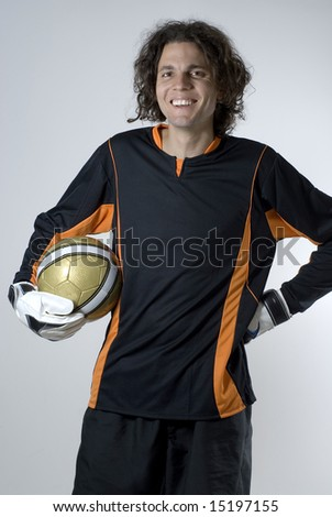 Goalie holding a soccer ball.  He is smiling and looking at the camera.  Vertically framed shot. - stock photo