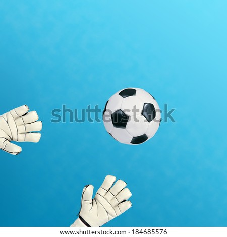 Goalkeeper catches the ball on blue background - stock photo