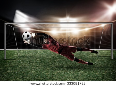Goalkeeper in gates jumping to catching ball - stock photo